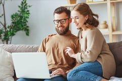 Ευτυχές ζεύγος με το φορητό προσωπικό υπολογιστή στο σπίτι στοκ φωτογραφία με δικαίωμα ελεύθερης χρήσης