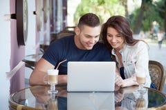 Ευτυχές ζεύγος με το lap-top σε έναν καφέ Στοκ φωτογραφία με δικαίωμα ελεύθερης χρήσης