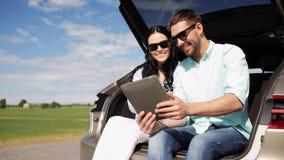 Ευτυχές ζεύγος με το PC ταμπλετών στον κορμό 21 αυτοκινήτων hatchback απόθεμα βίντεο