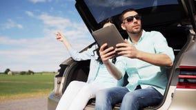 Ευτυχές ζεύγος με το PC ταμπλετών στον κορμό 23 αυτοκινήτων hatchback απόθεμα βίντεο