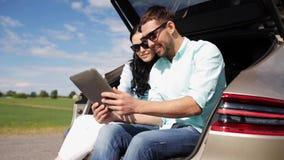 Ευτυχές ζεύγος με το PC ταμπλετών στον κορμό 32 αυτοκινήτων hatchback απόθεμα βίντεο