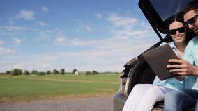 Ευτυχές ζεύγος με το PC ταμπλετών στον κορμό 36 αυτοκινήτων hatchback απόθεμα βίντεο