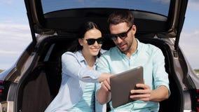 Ευτυχές ζεύγος με το PC ταμπλετών στον κορμό 6 αυτοκινήτων hatchback απόθεμα βίντεο