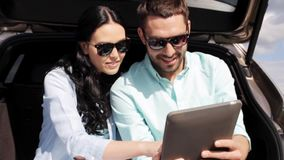 Ευτυχές ζεύγος με το PC ταμπλετών στον κορμό 2 αυτοκινήτων hatchback απόθεμα βίντεο