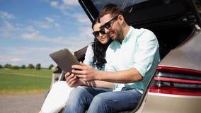 Ευτυχές ζεύγος με το PC ταμπλετών στον κορμό 20 αυτοκινήτων hatchback απόθεμα βίντεο