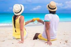Ευτυχές ζεύγος με δύο ποτήρια του χυμού από πορτοκάλι στις διακοπές παραλιών Στοκ Φωτογραφία
