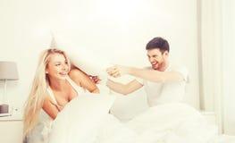 Ευτυχές ζεύγος που έχει την πάλη μαξιλαριών στο κρεβάτι στο σπίτι Στοκ Εικόνα