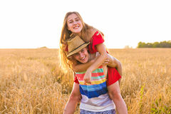 Ευτυχές ζεύγος που έχει τη διασκέδαση υπαίθρια στον τομέα σίτου πέρα από το ηλιοβασίλεμα Γελώντας χαρούμενη οικογένεια από κοινού Στοκ Εικόνα