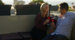 Ευτυχές ζεύγος που έχει το κόκκινο κρασί στο μπαλκόνι στο σπίτι 4k απόθεμα βίντεο