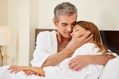 Ευτυχές ζεύγος που αγκαλιάζει στο κρεβάτι στοκ εικόνες με δικαίωμα ελεύθερης χρήσης