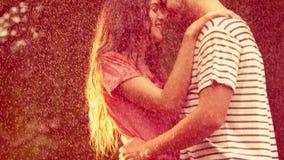 Ευτυχές ζεύγος που αγκαλιάζει στο πάρκο κατά τη διάρκεια της βροχής φιλμ μικρού μήκους