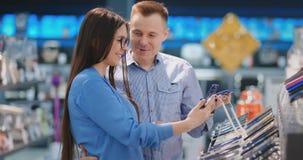 Ευτυχές ζεύγος που αγοράζει το νέο έξυπνο τηλέφωνο στο κατάστημα τεχνολογίας Απόφαση ποιου προτύπου στην αγορά απόθεμα βίντεο