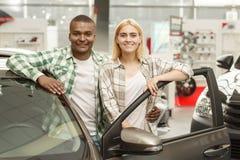 Ευτυχές ζεύγος που αγοράζει το νέο αυτοκίνητο μαζί στον αντιπρόσωπο στοκ εικόνα