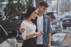 Ευτυχές ζεύγος που αγοράζει το νέο αυτοκίνητο στο σαλόνι αντιπροσώπων στοκ φωτογραφίες με δικαίωμα ελεύθερης χρήσης