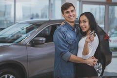 Ευτυχές ζεύγος που αγοράζει το νέο αυτοκίνητο στο σαλόνι αντιπροσώπων στοκ εικόνα