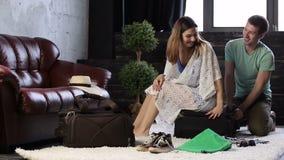 Ευτυχές ζεύγος που αγωνίζεται να κλείσει τη γεμισμένη βαλίτσα φιλμ μικρού μήκους