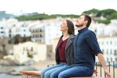 Ευτυχές ζεύγος που αναπνέει σε μια προεξοχή στις διακοπές στοκ εικόνα με δικαίωμα ελεύθερης χρήσης