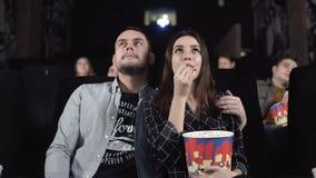 Ευτυχές ζεύγος που απολαμβάνει την ημερομηνία τους στον κινηματογράφο που προσέχει έναν κινηματογράφο απόθεμα βίντεο