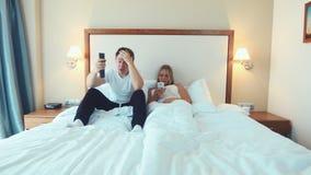 Ευτυχές ζεύγος που βρίσκεται στο κρεβάτι που προσέχει τη TV και το smartphone χρήσης απόθεμα βίντεο