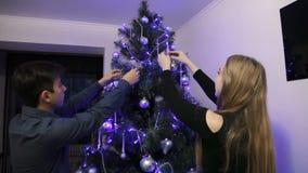 Ευτυχές ζεύγος που διακοσμεί το χριστουγεννιάτικο δέντρο στο σπίτι τους απόθεμα βίντεο