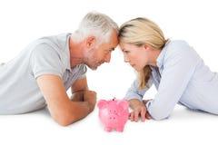 Ευτυχές ζεύγος που εναπόκειται στη piggy τράπεζα Στοκ Φωτογραφίες