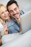 Ευτυχές ζεύγος που εξετάζει στο σπίτι την ταμπλέτα στοκ φωτογραφία