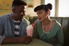 Ευτυχές ζεύγος που εξετάζει το ένα το άλλο ενώ έχοντας milkshake στοκ εικόνα με δικαίωμα ελεύθερης χρήσης