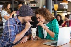 Ευτυχές ζεύγος που εξετάζει το ένα το άλλο ενώ έχοντας milkshake στοκ φωτογραφία με δικαίωμα ελεύθερης χρήσης
