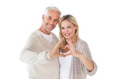 Ευτυχές ζεύγος που διαμορφώνει τη μορφή καρδιών με τα χέρια Στοκ εικόνα με δικαίωμα ελεύθερης χρήσης