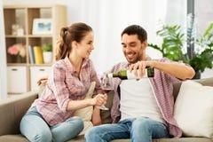 Ευτυχές ζεύγος που πίνει το κόκκινο κρασί στο σπίτι στοκ φωτογραφία