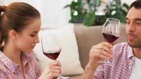 Ευτυχές ζεύγος που πίνει το κόκκινο κρασί στο σπίτι απόθεμα βίντεο