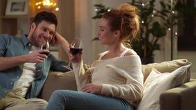 Ευτυχές ζεύγος που πίνει το κόκκινο κρασί στο σπίτι το βράδυ φιλμ μικρού μήκους