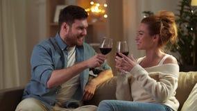 Ευτυχές ζεύγος που πίνει το κόκκινο κρασί στο σπίτι το βράδυ απόθεμα βίντεο