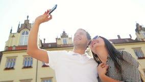 Ευτυχές ζεύγος που παίρνει Selfie χρησιμοποιώντας Smartphone που στέκεται στο παλαιό τετράγωνο πόλεων στο υπόβαθρο κτηρίων κατά τ απόθεμα βίντεο