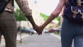 Ευτυχές ζεύγος που περπατά στα χέρια εκμετάλλευσης πόλεων, που ταξιδεύουν μαζί, υπαίθρια ημερομηνία φιλμ μικρού μήκους