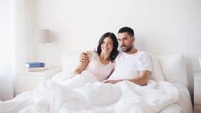 Ευτυχές ζεύγος που προσέχει τη TV στο κρεβάτι στο σπίτι φιλμ μικρού μήκους