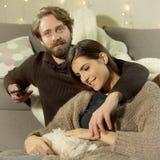 Ευτυχές ζεύγος που προσέχει τη TV στο σπίτι λίγο σκυλί στοκ φωτογραφία με δικαίωμα ελεύθερης χρήσης