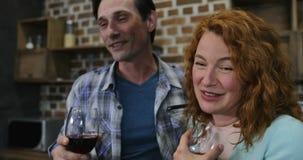 Ευτυχές ζεύγος που στέκεται κόκκινο κρασί επιτραπέζιων στο ομιλούν ποτών κουζινών, τον ευτυχή χαμογελώντας άνδρα και το αγκάλιασμ απόθεμα βίντεο