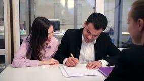 Ευτυχές ζεύγος που υπογράφει την ακίνητη σύμβαση απόθεμα βίντεο