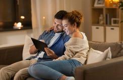 Ευτυχές ζεύγος που χρησιμοποιεί το PC ταμπλετών στο σπίτι το βράδυ στοκ εικόνα