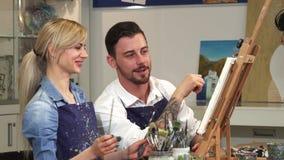 Ευτυχές ζεύγος που χρωματίζει μια εικόνα μαζί κατά μια ημερομηνία στο στούντιο τέχνης ελεύθερη απεικόνιση δικαιώματος