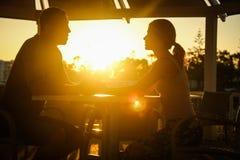 Ευτυχές ζεύγος σε έναν πίνακα θαλασσίως στη φύση ηλιοβασιλέματος στοκ φωτογραφία
