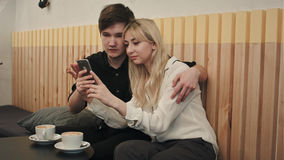 Ευτυχές ζεύγος σε ένα σπίτι καφέ που έχει το πρόγευμα και και που χρησιμοποιεί το τηλέφωνο κυττάρων Στοκ Εικόνες
