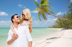 Ευτυχές ζεύγος στα γυαλιά ηλίου πέρα από τη θερινή παραλία στοκ εικόνα
