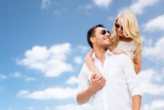 Ευτυχές ζεύγος στα γυαλιά ηλίου πέρα από το μπλε ουρανό στοκ φωτογραφία