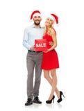 Ευτυχές ζεύγος στα καπέλα santa με το κόκκινο σημάδι πώλησης Στοκ Εικόνες