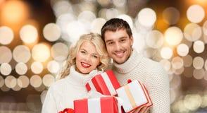 Ευτυχές ζεύγος στα πουλόβερ που κρατά τα δώρα Χριστουγέννων Στοκ Φωτογραφία