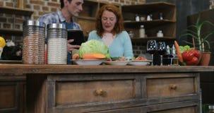 Ευτυχές ζεύγος στην κουζίνα που μαγειρεύει χρησιμοποιώντας τον ψηφιακούς άνδρα και τη γυναίκα ταμπλετών που προετοιμάζουν τα τρόφ απόθεμα βίντεο