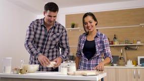 Ευτυχές ζεύγος στην κουζίνα που προετοιμάζει τα τρόφιμα από κοινού απόθεμα βίντεο