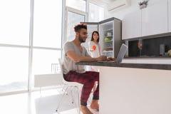 Ευτυχές ζεύγος στην κουζίνα που χρησιμοποιεί το σύγχρονο διαμέρισμα φορητών προσωπικών υπολογιστών με το πανοραμικό παράθυρο Στοκ Φωτογραφίες